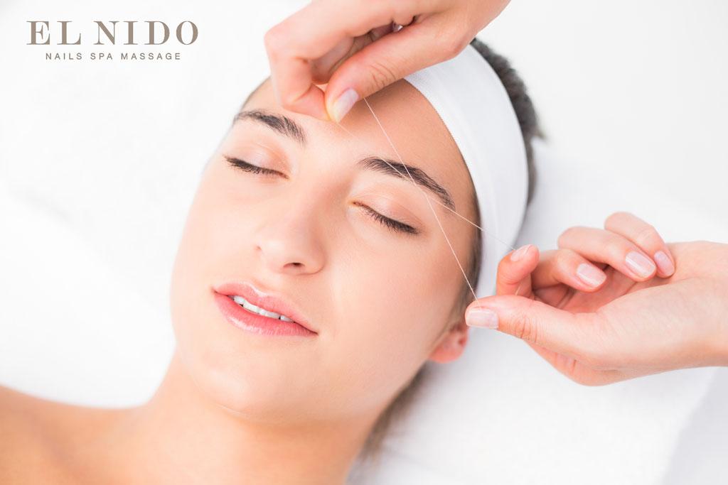 foto de una chica mientras le depilan con hilo una ceja