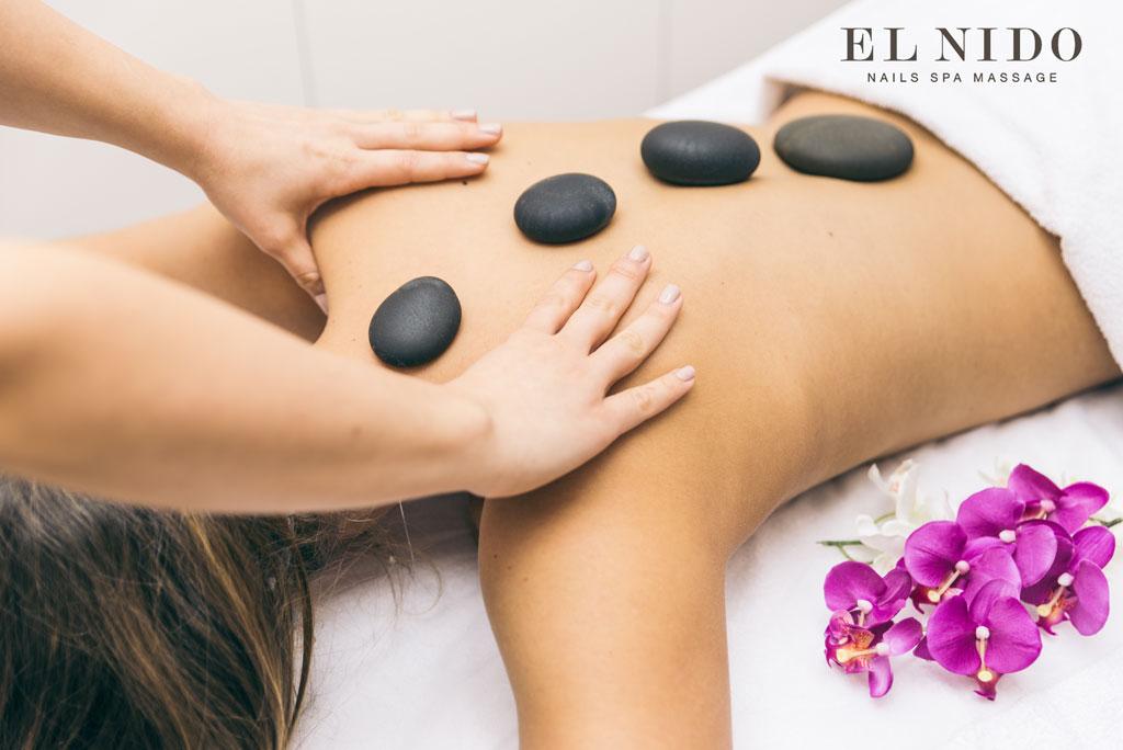 chica tumbada en una camilla de masaje en barcelona con piedras en la columna